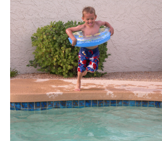 Child jumping into clean pool
